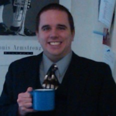 Picture of former student Keven D. dressed in a buisiness suit holding coffee
