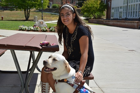 Student Stephanie V sitting outside with her service dog, Luna