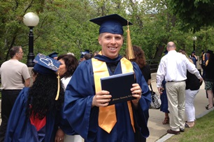 Former student Tyler L. holding diploma Commencement Day