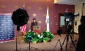camera set up in front of woman wearing cap and gown standing behind a podium