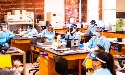 students wearing masks, face shields and medical gowns work in lab