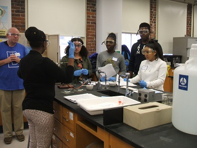 Students in a science lab looking at an instructor demonstrating a procedure